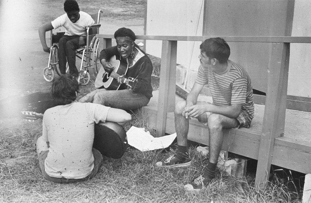 Imagem em preto e branco do filme Crip Camp: Revolução pela Inclusão. A fotografia registra um grupo de quatro jovens, um deles com deficiência física usando uma cadeira de rodas, que está mais à esquerda e acima da imagem. Os demais estão sentados numa passarela de madeira sob o chão de gramado, tocando violão e cantando.