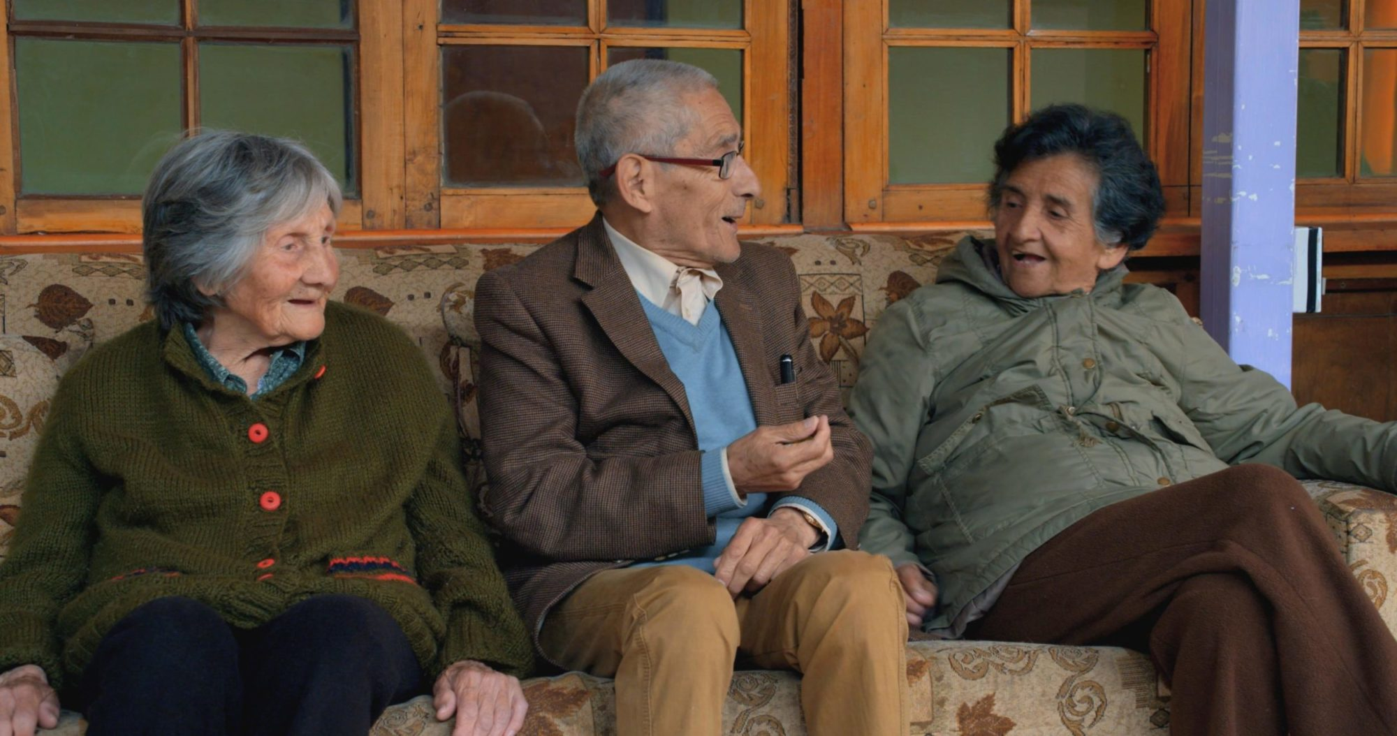 A foto mostra três pessoas idosas sentadas em um sofá bege estampado, sendo duas mulheres com um homem sentado ao centro. A senhora da esquerda tem cabelos grisalhos e veste uma blusa de botão verde-musgo, O senhor de cabelo curto e branco veste um terno marrom sobre um pulôver azul claro. Ele faz um gesto mostrando para a mulher da direita, que veste uma jaqueta abotoada cinza e tem cabelos grisalhos escuros. Os três sorriem. Atrás são vistas janelas de vidro que dão para um ambiente interno, indicando que se encontram em um ambiente externo.