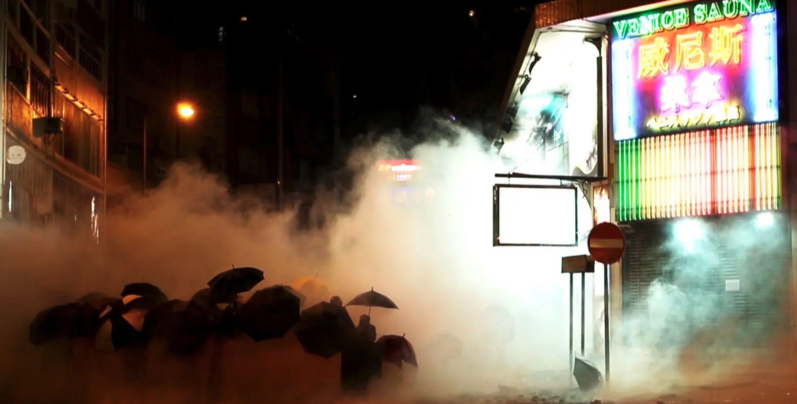 Cena do curta Do Not Split. Em meio a fumaça de gás lacrimogêneo, podemos ver vários manifestantes pró-Hong Kong segurando guarda chuvas. Eles estão em uma rua, é noite, e há um edifício comercial ao lado direito.
