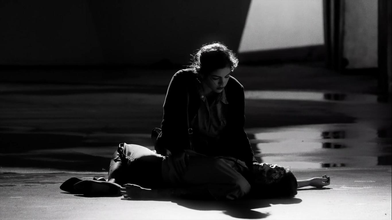 Cena do curta Fantasma Magnético. Em preto-e-branco, vemos uma mulher montada em cima de um corpo desacordado. Ela olha atentamente para a cabeça do corpo.