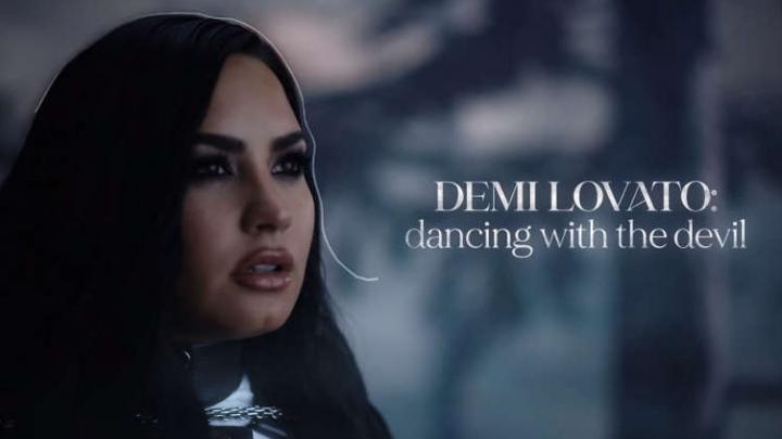 """Foto retangular da chamada do documentário Dancing With The Devil. No lado esquerdo, está a cantora Demi Lovato, do peito para cima. Ela é branca, possui cabelos pretos compridos ondulados e olhos castanhos escuros, quase pretos. Ela está maquiada, com os olhos bem marcados de preto. Na boca, ela usa um batom marrom cintilante e está semiaberta. Seu corpo está ligeiramente virado para a direita, olhando para cima. No lado direito, mais centralizado, está escrito """"Demi Lovato:"""" com letras brancas e maiúsculas. Logo abaixo, está escrito """"dancing with the devil"""" em letras minúsculas e brancas. O fundo está borrado, mas é possível enxergar uma parte de um tronco estreito de uma árvore, com muitos galhos e folhas."""