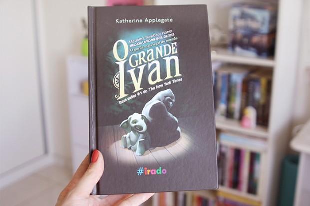 """Foto retangular. Ao centro, está o livro """"O grande Ivan"""". No canto superior da capa, está escrito Katherine Applegate. O título """"O grande Ivan"""" possui cada palavra escrita embaixo da outra. Do lado da letra """"O"""", está escrito """"Medalha Newbery Honor"""" seguido de """"Melhor Livro Infantil de 2013"""" e """"O gorila mais legal do mundo"""". Embaixo do nome Ivan, está escrito """"Best-seller #1 do The New York Times"""". Embaixo dos escritos, tem um gorila e um filhote de elefante, sentado um de costas por outro, mas se olhando. O elefante é cinza e o gorila é da espécie costas prateadas. Há um holofote sobre os dois. Embaixo dos dois, está escrito """"#irado"""". Cada letra possui uma cor, sendo elas azul, vermelho, amarelo, rosa, verde e roxo, respectivamente. Uma mão direita segura o livro, com o polegar apoiado sobre a capa. A unha está pintada de vermelho. O fundo da foto está borrado. Possui uma mobília branca com gavetas, uma estante branca de três prateleiras com vários livros e o canto de uma bancada também branca, respectivamente. Do lado esquerdo, tem um armário de porta de correr branco."""
