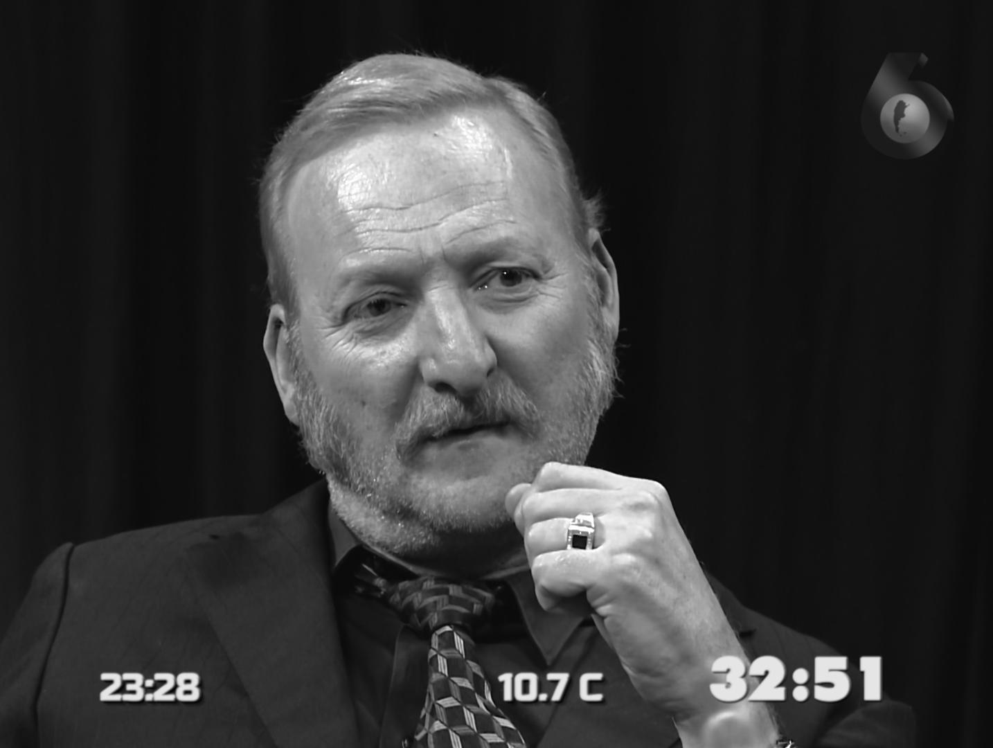 Cena do filme História do Oculto. Nela, vemos um homem idoso, branco e de barba grisalha. A imagem é um close de seu busto, e está em preto-e-branco. Ele veste um terno e usa um anel no dedo anelar esquerdo. Na parte de baixo da imagem vemos informações escritas: 23:28, 10.7c e 32:51