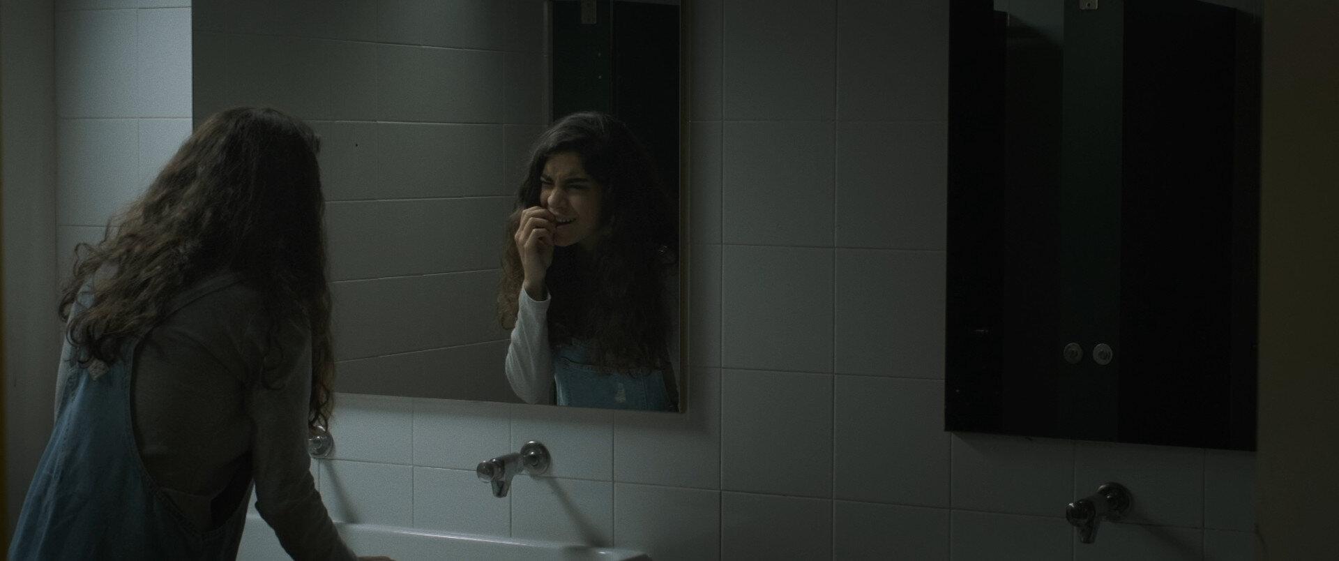 Cena do curta Horrorscope. Nela, vemos uma mulher branca se olhando no espelho e cutucando o dente.