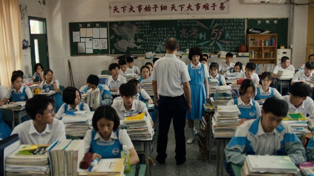 Cena do filme Better Days. A imagem é de uma sala de aula, com cerca de 30 alunos, todos jovens amarelos vestindo uniformes brancos e azuis. Eles estão sentados em cadeiras com mesas cheias de livros. No centro da sala, o professor está de costas para a câmera e está de frente para a atriz Zhou Dongyu, uma mulher jovem amarela que possui cabelo curto preto liso. O professor chama a atenção de Zhou.