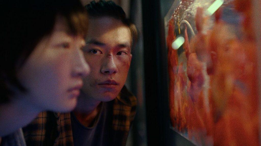 Cena do filme Better Days. Na imagem vemos os atores da esquerda para direita Zhou Dongyu, uma mulher jovem amarela e está desfocada; e Jackson Yee, um homem jovem amarelo. Jackson veste uma blusa amarela xadrez, está com o rosto machucado e olha para Zhou. Ele possui cabelo preto liso e está preso em um rabo de cavalo. Zhou veste um casaco cinza claro e possui cabelo curto preto liso. Ela olha para um aquário de peixes vermelhos.