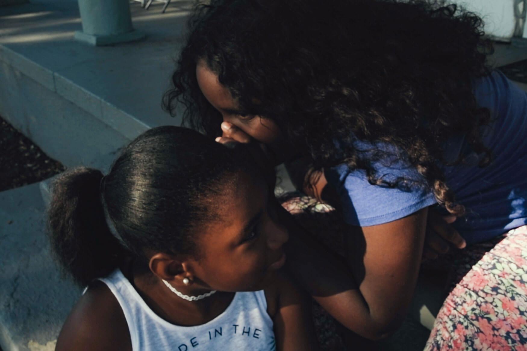 Cena do documentário Uma Canção para Latasha. Nesta imagem, vemos duas garotas negras que aparentam ter 12 anos. A garota da direita está cochichando no ouvido da garota da direita. A garota da direita está com os cabelos soltos e veste camiseta roxa. A menina da esquerda está com os cabelos amarrados e veste camiseta regata branca. Elas estão sentadas uma do lado da outra em uma varanda de uma casa.