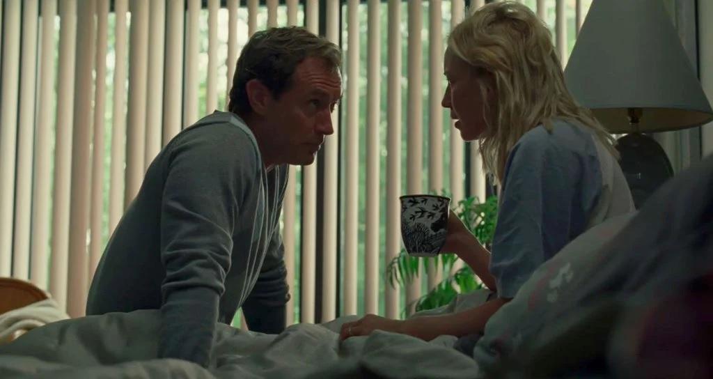 Cena do filme O Refúgio. Na cena estão os personagens Rory, interpretado por Jude Law, e Alisson, interpretada por Carrie Coon, que se olham, estando um de frente para o outro. Os dois estão sentados na cama e trajados de roupas azul clara. O ambiente é iluminado, a cortina de persiana lateral está aberta. Alisson está com um edredom branco nas pernas, ela segura uma caneca com estampas azuis e brancas e ao seu lado se encontra um abajur desligado.