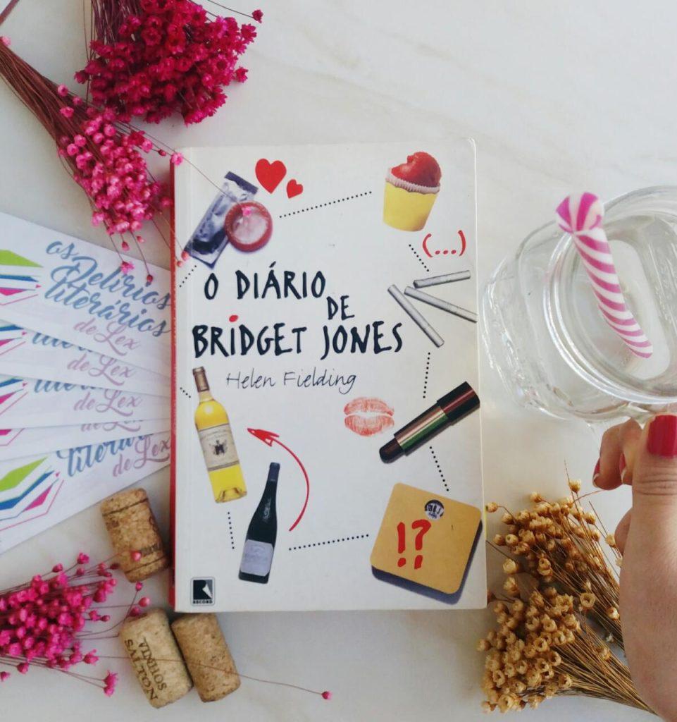 Foto do livro O Diário de Bridget Jones, por Helen Fielding. O livro está centralizado, possui capa branco com escritos pretos e fotos de camisinhas, garrafas e batons na capa. Ao redor, foram posicionados marca-páginas e flores para compor o cenário também de fundo branco.