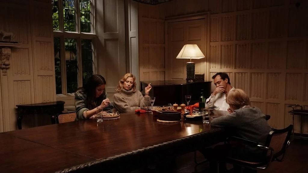 Cena do filme O Refúgio. Nela se encontram os personagens da família O'Hara sentados em uma grande mesa de madeira, o ambiente é mal iluminado, sendo a iluminação vinda da janela e de um lustre ao fundo. Os filhos Sam e Ben, interpretados por Oona Roche e Charlie Shotwell estão comendo, enquanto Alisson, interpretada por Carrie Coon está fumando um cigarro e Rory, Jude Law, está com a mão no queixo, com um semblante de irritação. Alisson tem uma expressão facial reprovação. O garoto está vestido com uma blusa de frio, a menina com uma blusa de lã listrada em tons de cinza, a mãe usa uma blusa cinza de lã e o pai está com uma camisa social branca.