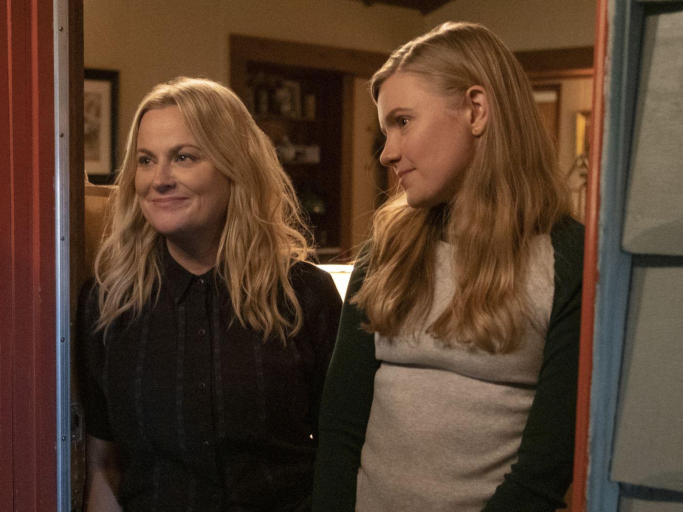 Cena do filme na qual estão em tela, da esquerda para a direita, Lisa (Amy Poehler) e Vivan (Hadley Robinson) na porta da casa das personagens. Lisa é uma mulher adulta, branca, loira, de olhos claros, mais baixa que a filha, usa uma camisa preta e sorri sem mostrar os dentes. Vivian está ao lado quase em perfil. É uma adolescente loira e branca, que usa uma blusa cinza com um moletom preto.