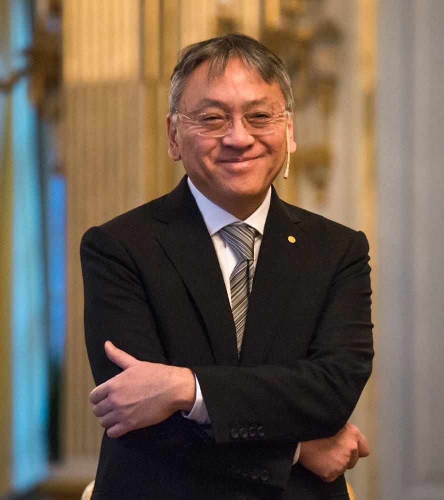 Foto do escritor Kazuo Ishiguro. Ele é um homem ásiatico com cabelos brancos e olhos castanhos, ele usa um óculos fino, veste um terno preto com uma gravata listrada. O fundo atrás do autor é desfocado.