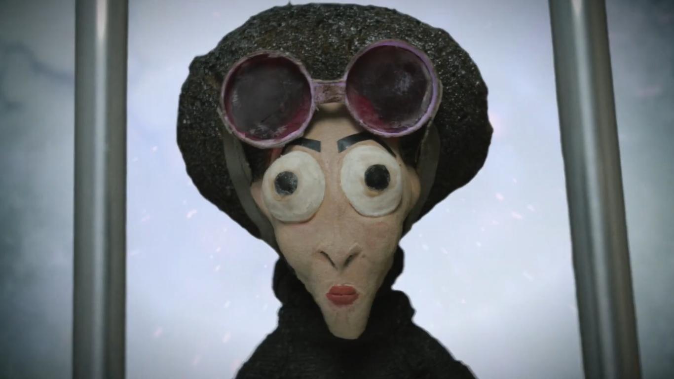 Cena da animação Missão Berço Esplêndido. Uma mulher está no centro da imagem, do busto para cima. Ela possui um queixo pontudo e grandes olhos esbugalhados. Seu cabelo é grande e crespo. Uma viseira redonda está na sua cabeça.