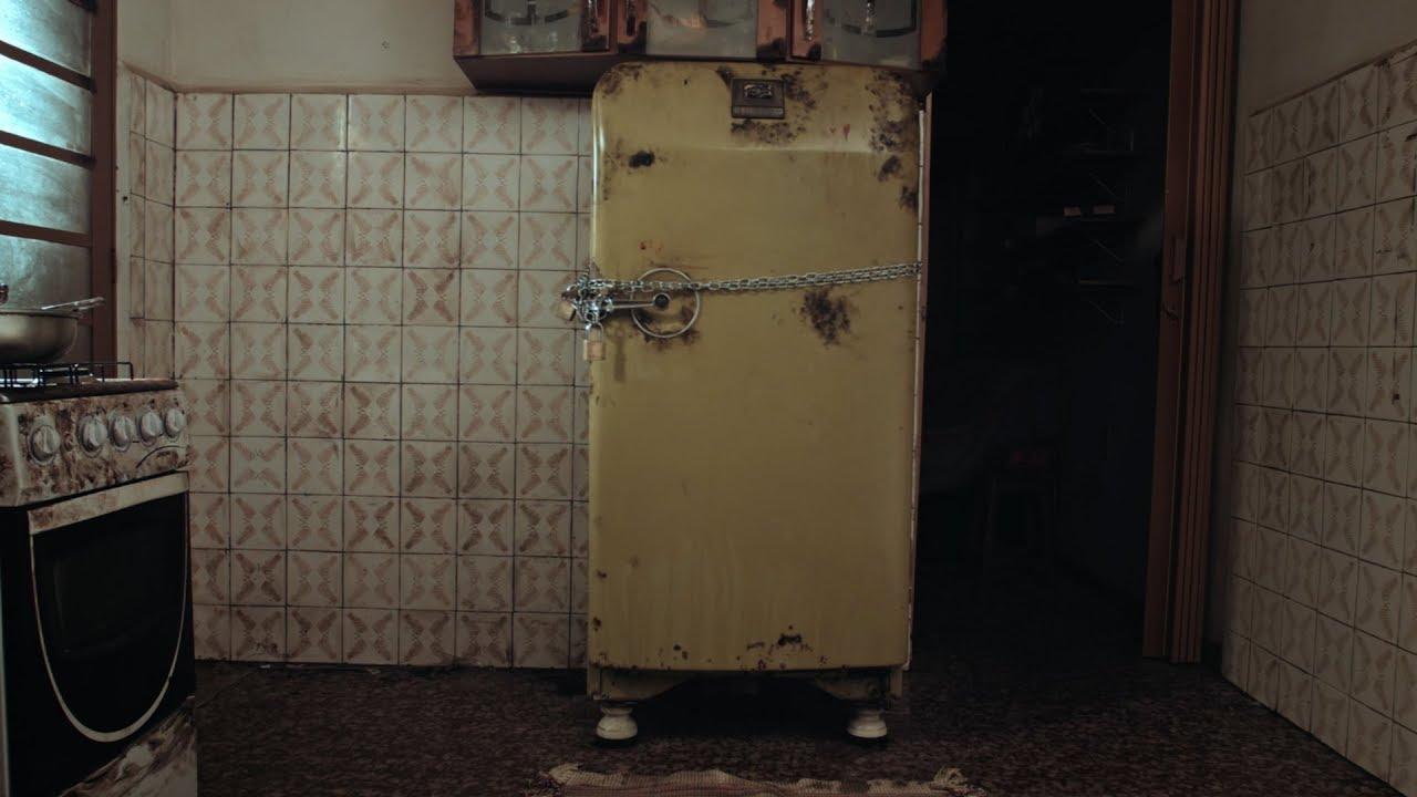 Cena do curta Nervo. Nela, vemos uma geladeira amarela trancafiada. O cenário da cozinha é de sujeira extrema.