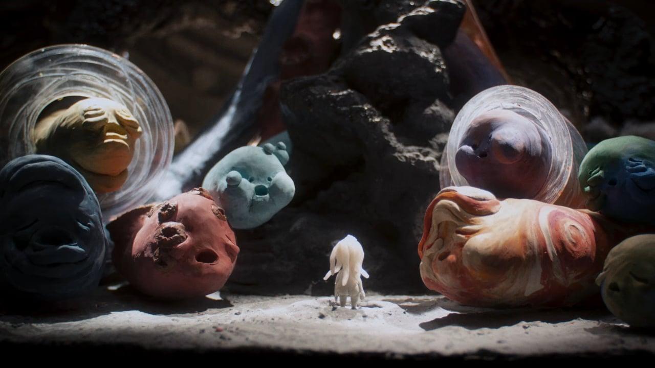 Cena da animação O Black Hole. Com personagens de massinha, vemos uma bonequinha branca com cabelos compridos. Ela está de costas e olha para grandes bonecos em formatos de minhocas. Eles variam entre azul, amarelo, laranja e vermelho.
