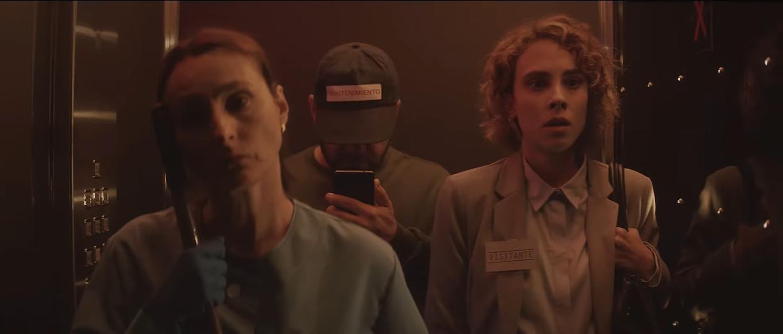 Cena do curta Oculto. Dentro de um elevador, vemos 3 pessoas. Uma mulher de azul, luvas azuis e cabelo preto, uma loira com terninho social e um homem de boné, olhando seu celular. A imagem tem um filtro avermelhado.