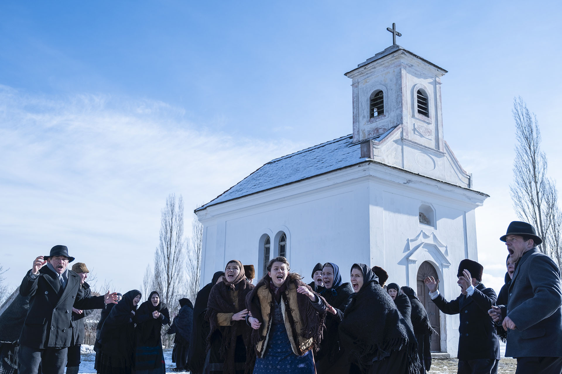Cena do filme Post Mortem. Nela, vemos uma porção de homens e mulheres reunidos frente a uma igreja. A igreja é branca, e o céu contrasta com um azul claro, enquanto todas as pessoas vestem roupas escuras.