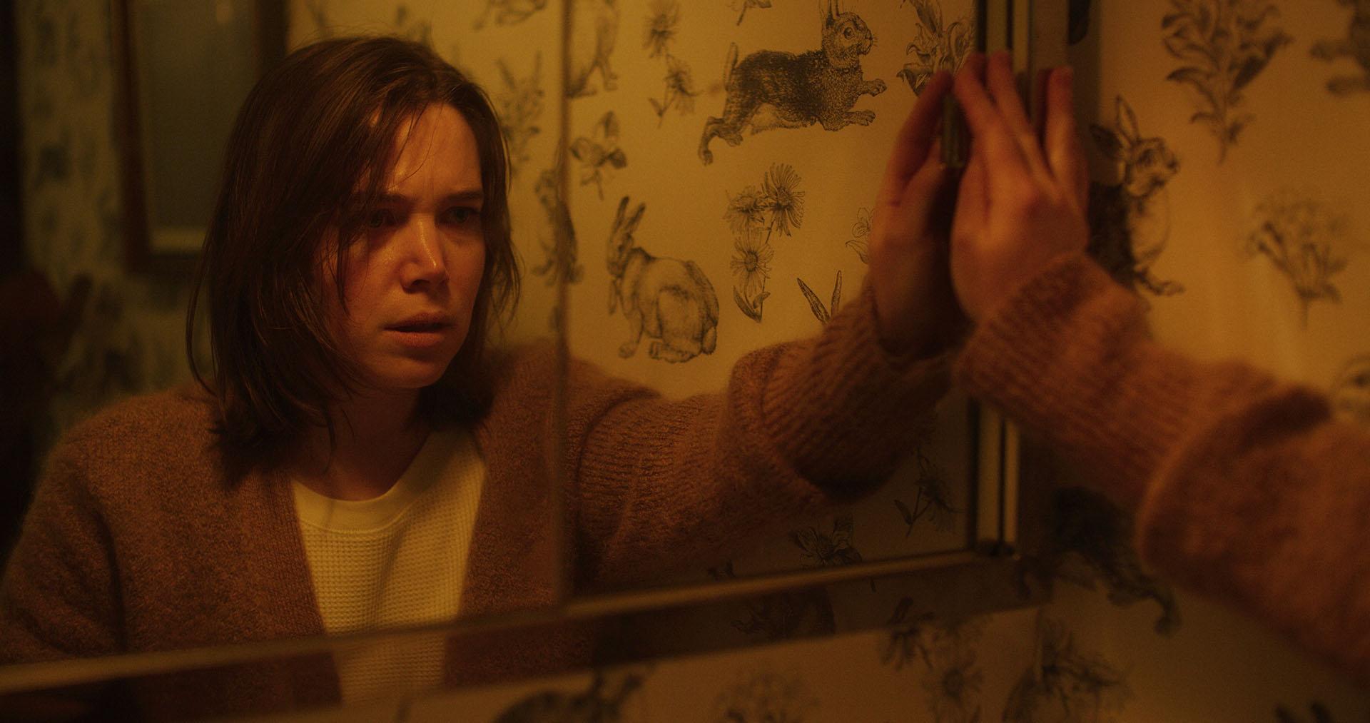 Cna do filme Sangre Comigo. Nela, vemos uma mulher branca se olhando no espelho. A coloração da cena é amarela, e ela veste um suéter marrom, seus olhos exprimem medo.
