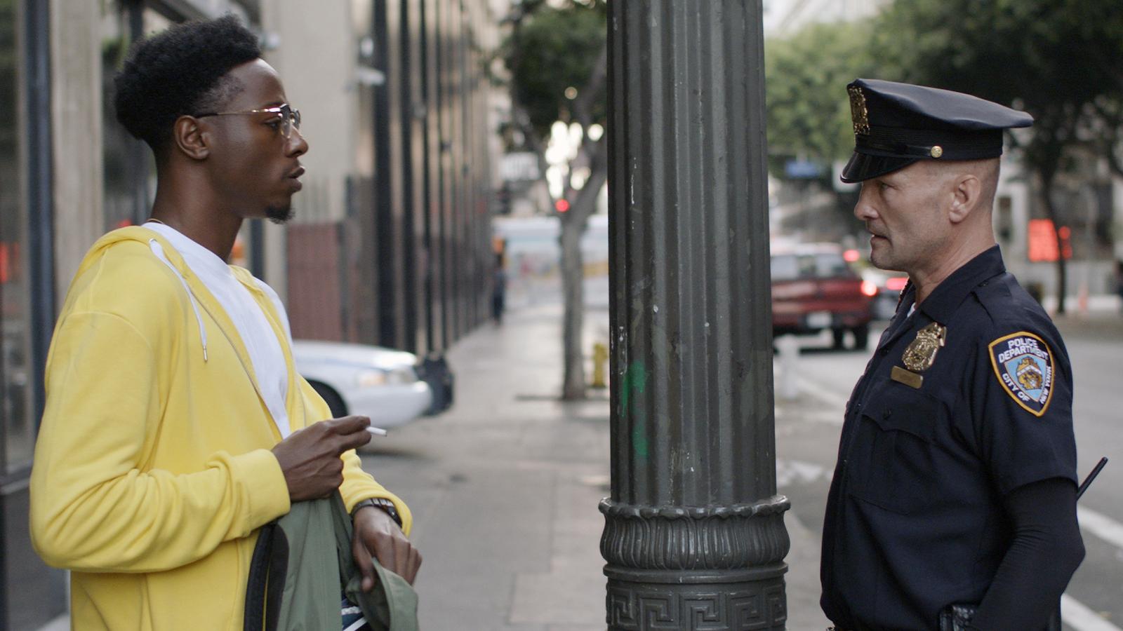 Cena do curta Dois Estranhos. Dois homens se encaram de perfil. À esquerda está Joey Badass, um homem negro de 26 anos que usa óculos, uma jaqueta amarela e blusa branca por baixo. Joey segura um cigarro na mão direita e está com sua mochila aberta nas mãos. À direita está Andrew Howard, um homem branco de 51 anos que usa uniforme policial - roupa e quepe azul escuro com símbolos da polícia de Nova Iorque. Ao fundo, o cenário é urbano e há um poste de luz no meio dos dois personagens.