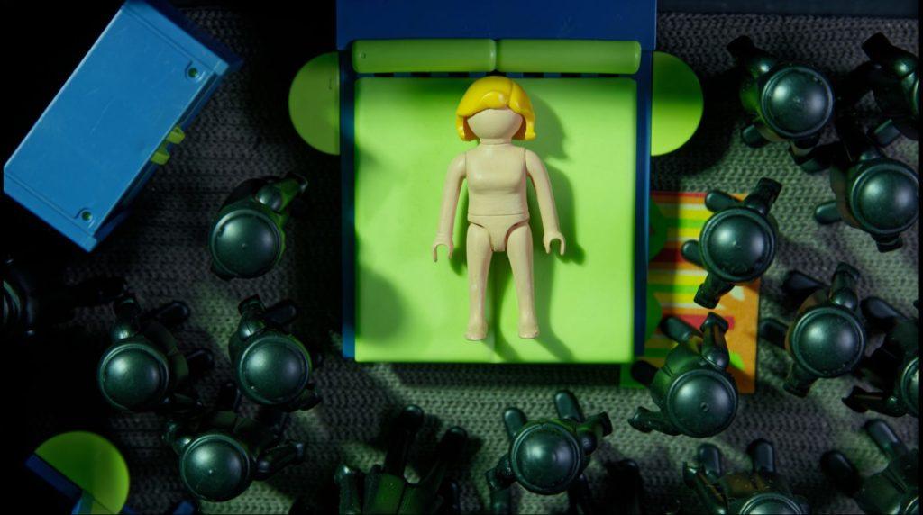 Cena da animação The Wedding Cake. Os personagens são todos bonequinhos de plástico. No centro, há uma mulher deitada em uma cama verde e azul. Ela é loira e está nua. Ao redor dela, vários bonecos pretos estão de pé na direção da cama.