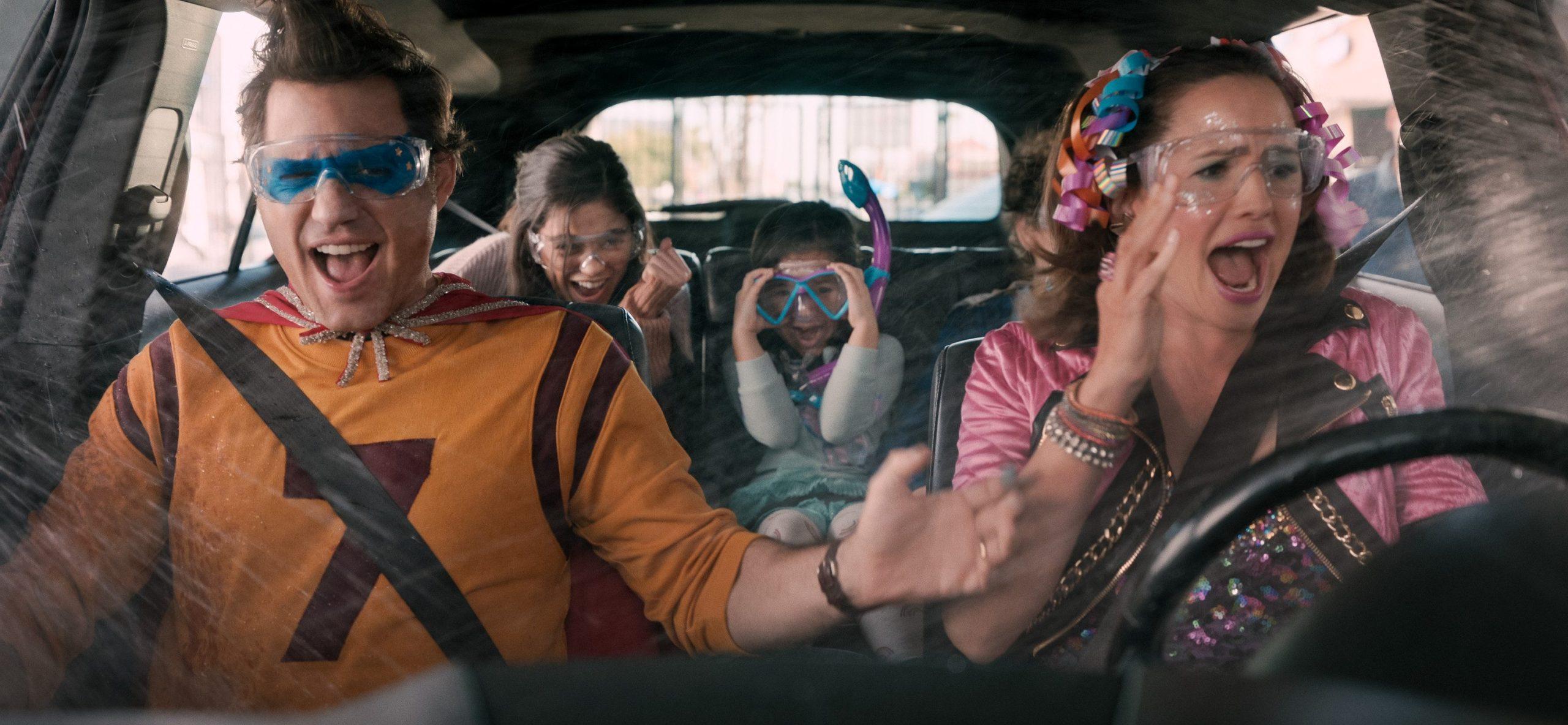 Cena do filme Dia do Sim. Os quatro personagens estão fantasiados em um carro com água sendo espirrada dentro. No volante, à direita, está Jennifer Garner, uma mulher branca adulta de cabelos castanhos escuros que usa uma roupa rosa e flores no cabelo. No banco do passageiro, Édgar Ramirez, uma homem branco de cabelos castanhos usa uma camisa laranja com o número 7 e óculos azul. No banco traseiro, à direita, está uma menina branca de cabelos castanhos com as mãos no rosto. Ao seu lado, sua irmã mais velha, uma jovem adolescente branca de cabelos castanhos, está com a cabeça abaixada;