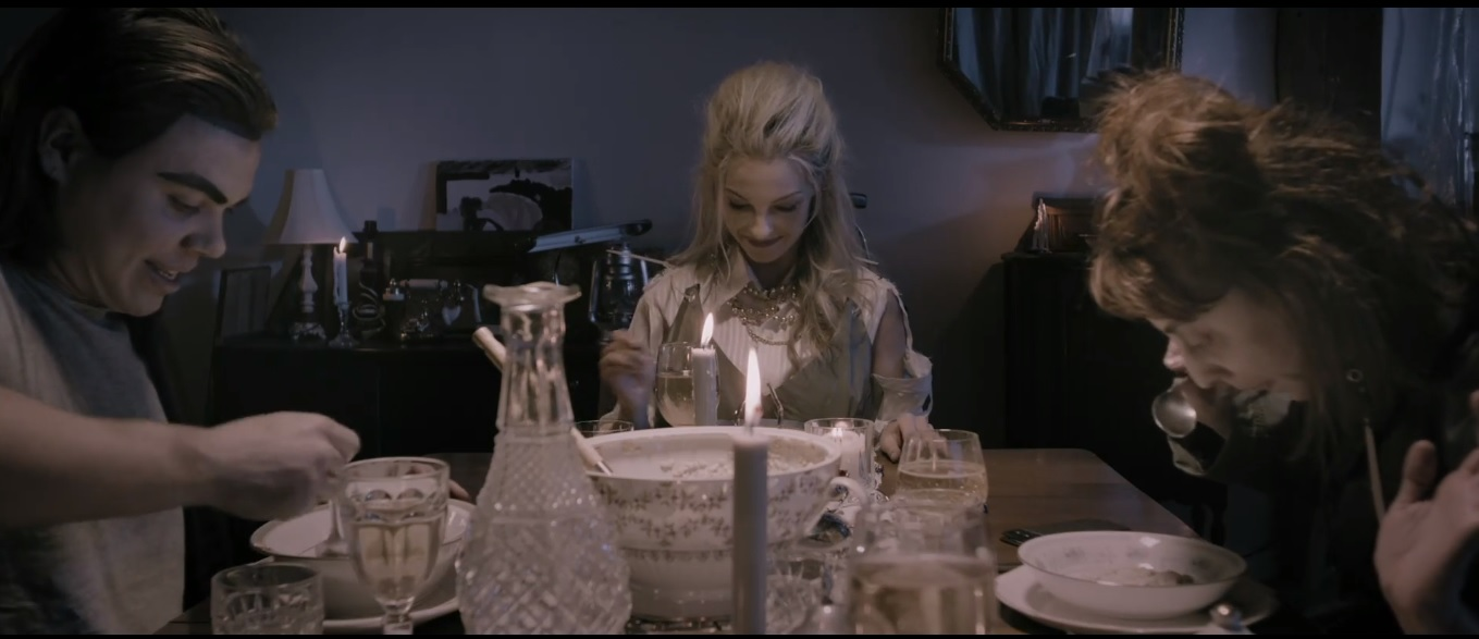 Foto do curta A Dinner Party. Nela, vemos três pessoas jantando à mesa. Os dois são jovens, tem pele branca leitosa e maquiagem sebosa. Todos os apetrechos da mesa são brancos, assim como a comida servida.