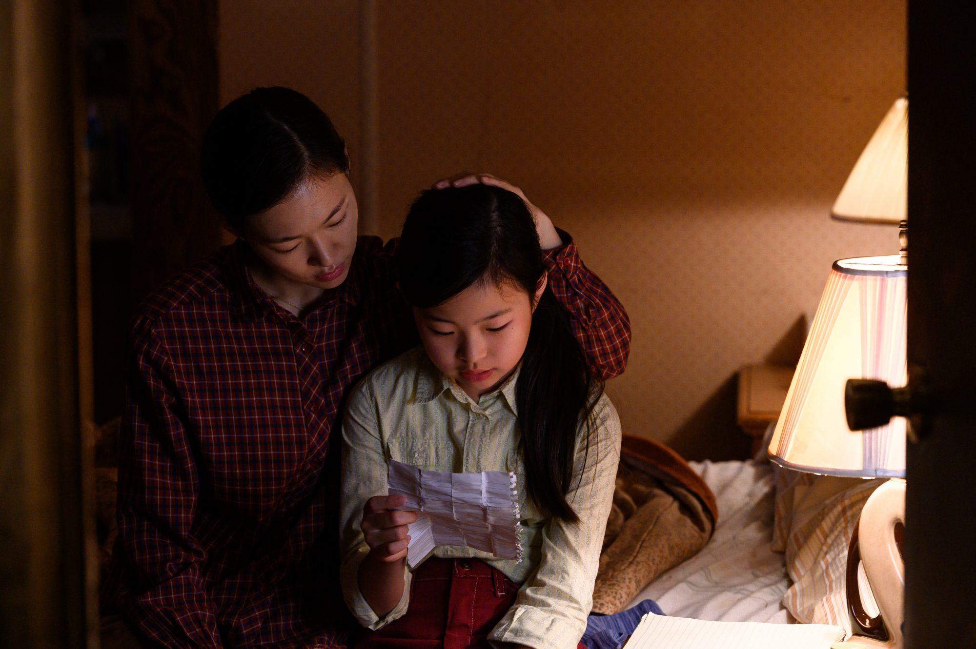 Cena do filme Minari. A imagem apresenta Monica, personagem da atriz asiática Ye-ri Han, e Anne, personagem da atriz mirim Noel Cho. Monica está sentada numa cama e Anne está no colo dela, lendo uma carta, enquanto a mãe acaricia seus cabelos. Monica veste uma camisa xadrez vermelha e Anne uma camisa bege. A imagem é iluminada por uma abajur do lado esquerdo da cena, onde também se vê a maçaneta de uma porta.