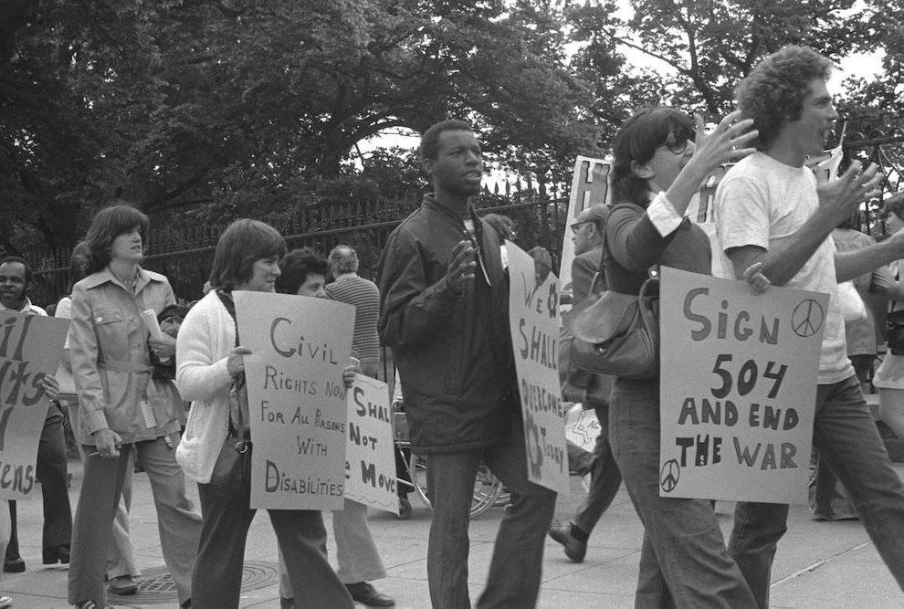 Imagem em preto e branco do filme Crip Camp: Revolução pela Inclusão. A fotografia registra uma passeata de um grupo de jovens. Eles estão em cerca de 10 pessoas e seguram cartazes de protesto enquanto caminham numa calçada. A imagem os registra de lado, enquanto caminham para o lado direito, e ao fundo existem muitas árvores e uma cerca de portão.