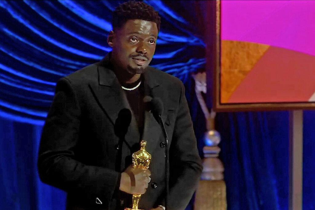 Foto de Daniel Kaluuya. O ator é negreo, de cabelos curtos. Ele veste uma jaqueta preta por cima de uma blusa preta, e um colar prateado. O homem segura a estatueta enquanto fala no microfone a sua frente. O fundo é azul com uma tela laranja.