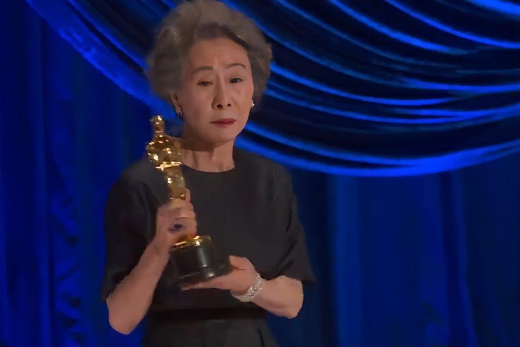 Foto de Yuh-Jung Youn. A mulher Asiatica, de cabelos brancos e curtos, veste um vestido azul escuro, e pulseira prateada. Ela segura a estatueta em suas mãos, com uma expressão séria. O fundo da imagem é azul.