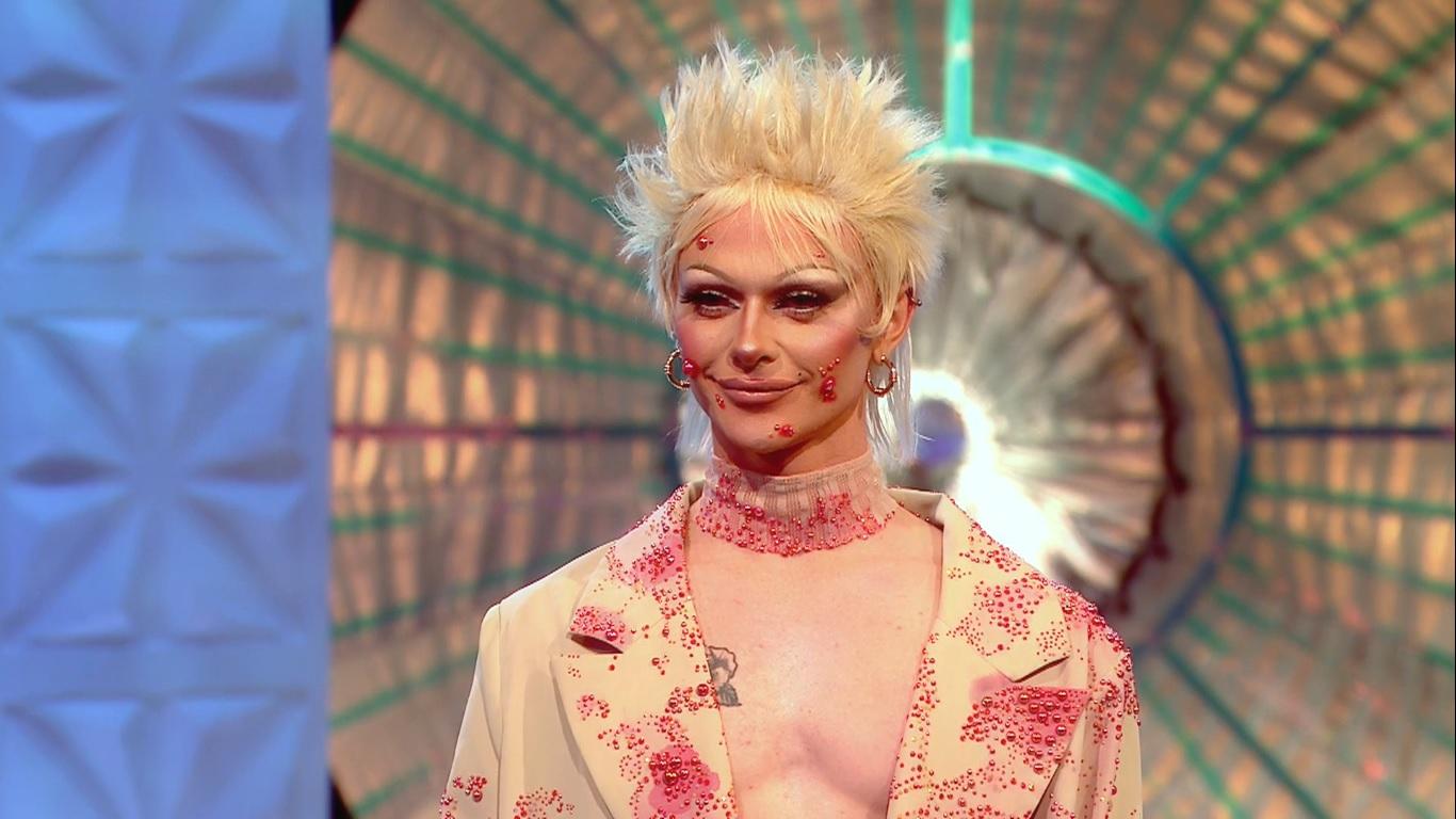 Foto de Bimini Bon Boulash, competidora de Drag Race UK. Ela é uma pessoa não-binária branca, e usa uma peruca loiro claro. Ela veste um blazer na cor da sua pele, com várias pedrinhas na cor vermelha, imitando espinhas. Sua maquiagem também possui as mesmas pedrinhas, com a mesma intenção de parecerem espinhas. Ao fundo, há um elemento do palco do show.