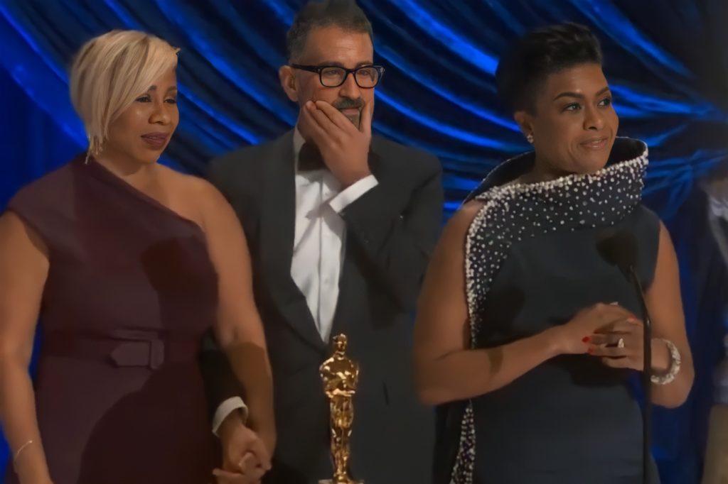 Foto de Sergio Lopez-Rivera, Mia Neal e Jamika Wilson. Na direita, Mia Neal fala no microfone a sua frente. A mulher negra está com os cabelos presos e veste um vestido azul, com brilhos nas bordas. Ao seu lado esquerdo, Sergio Lopez-Rivera, vestindo um terno preto e camisa branca, e Jamika Wilson, de vestido vinho com apenas uma manga, estão de mãos dadas. Na frente deles está a estatueta, e o fundo da foto é azul.