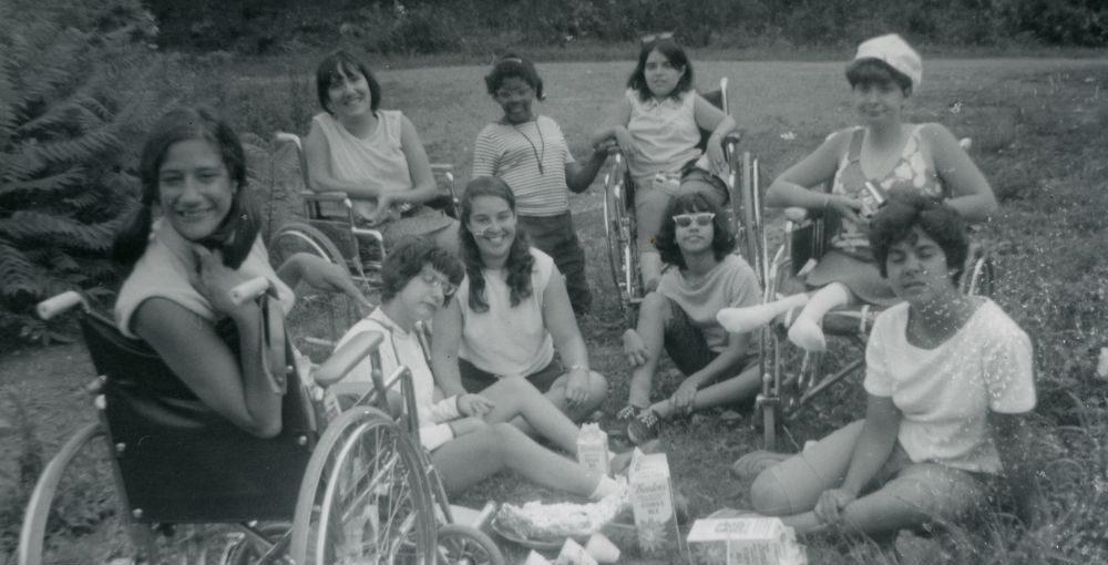 Imagem em preto e branco do filme Crip Camp: Revolução pela Inclusão. A fotografia registra um grupo de jovens mulheres campistas, que posam sorridentes para a câmera em um gramado.