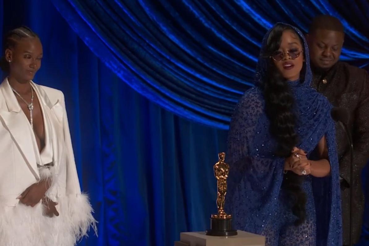 Foto de H.E.R. Dernst Emile II e Tiara Thomas. A cantora negra veste um vestido azul com brilho, óculos escuros roxos e o cabelo caído de lado. Ela fala no microfone à sua frente. Atras dela, Dernest, homem negro de terno preto, olha para baixo. Ao seu lado esquerdo está Tiara, mulher também negra, vestindo uma roupa branca e o cabelo preso em tranças, olhando para H.E.R. No centro da imagem há uma estatueta, e o fundo é azul.
