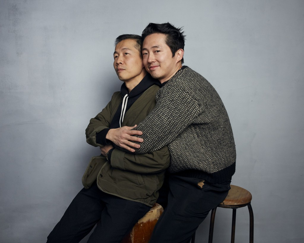 Fotografia de Lee Isaac Chung, diretor e roteirista de Minari, e Steven Yeun, protagonista do filme. Chung e Steven estão sentados na frente de um fundo cinza claro. Steven, um homem amarelo de cabelos curtos, veste uma blusa de lã branca e preta e uma calça escura, sorri para a foto e abraça Chung. O diretor, também amarelo, está sentado, vestindo uma blusa verde militar e calças pretas, e olha para cima, fora da imagem.