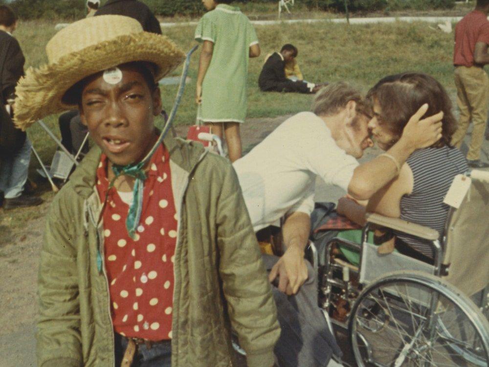 Imagem do filme Crip Camp: Revolução pela Inclusão. No lado esquerdo do registro, está um jovem negro vestindo um chapéu de palha e uma camisa de bolinhas vermelhas. Ele faz careta para imagem. No lado direto, atrás do primeiro jovem, está um casal de jovens. Ambos são brancos e usam cadeiras de roda enquanto se beijam. Ao fundo, pode-se observar um gramado e muitos outros jovens.