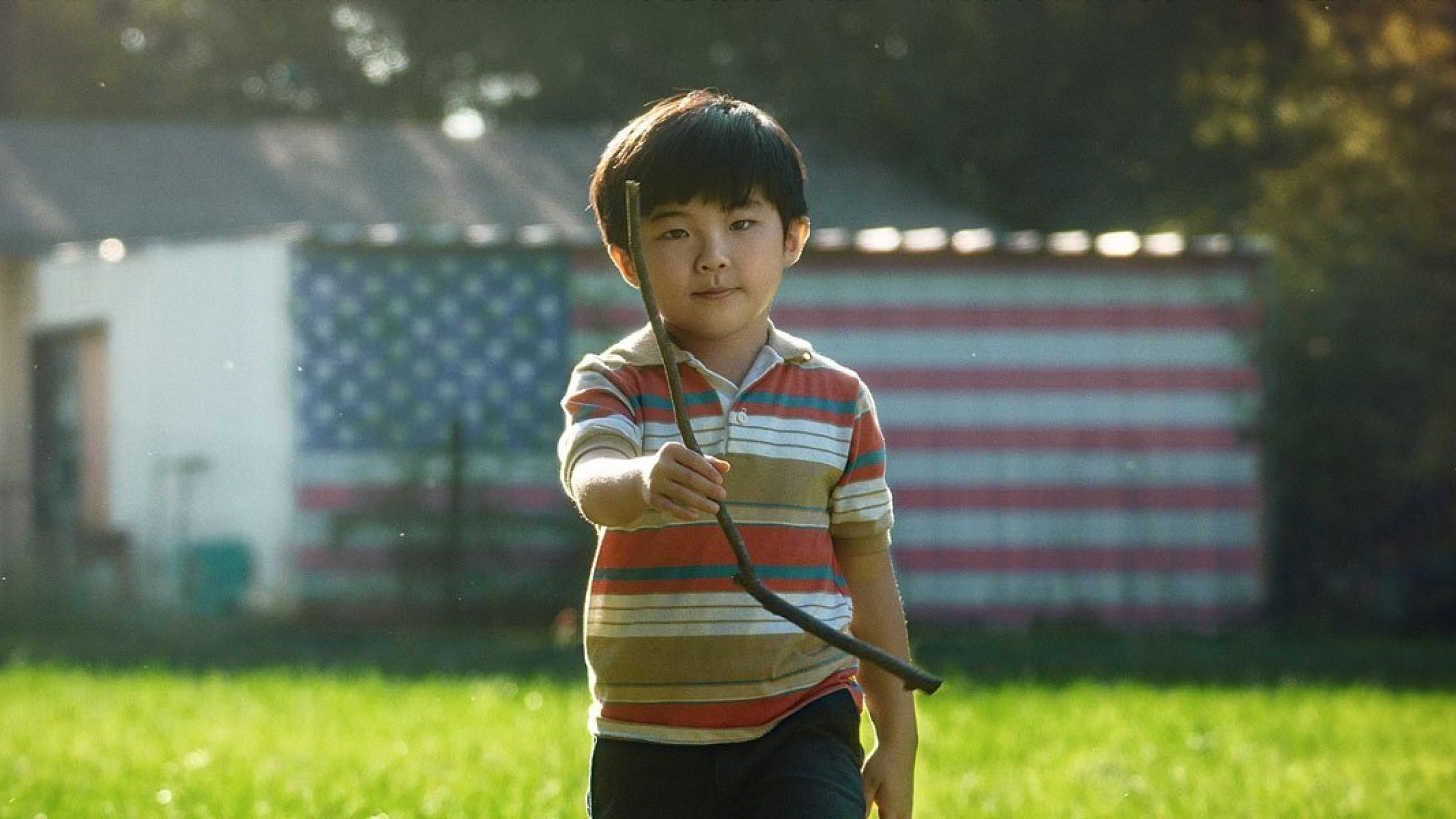 Imagem de divulgação do filme Minari. A imagem é retangular e mostra o personagem David, interpretado por Alan Kim, uma criança asiática de sete anos, de cabelos lisos escuros, ao centro. David veste uma camisa polo de listras em tons de marrom, branco, cinza e laranja, e uma bermuda cinza escura. O menino, fotografado do quadril para cima, olha para a câmera com uma expressão serena e segura um graveto com a mão direita, oferecendo-o para a câmera. Atrás dele, existe uma casinha com uma pintura da bandeira dos Estados Unidos na parede, e ele caminha sob um gramado verde. A imagem é colorida vibrante.