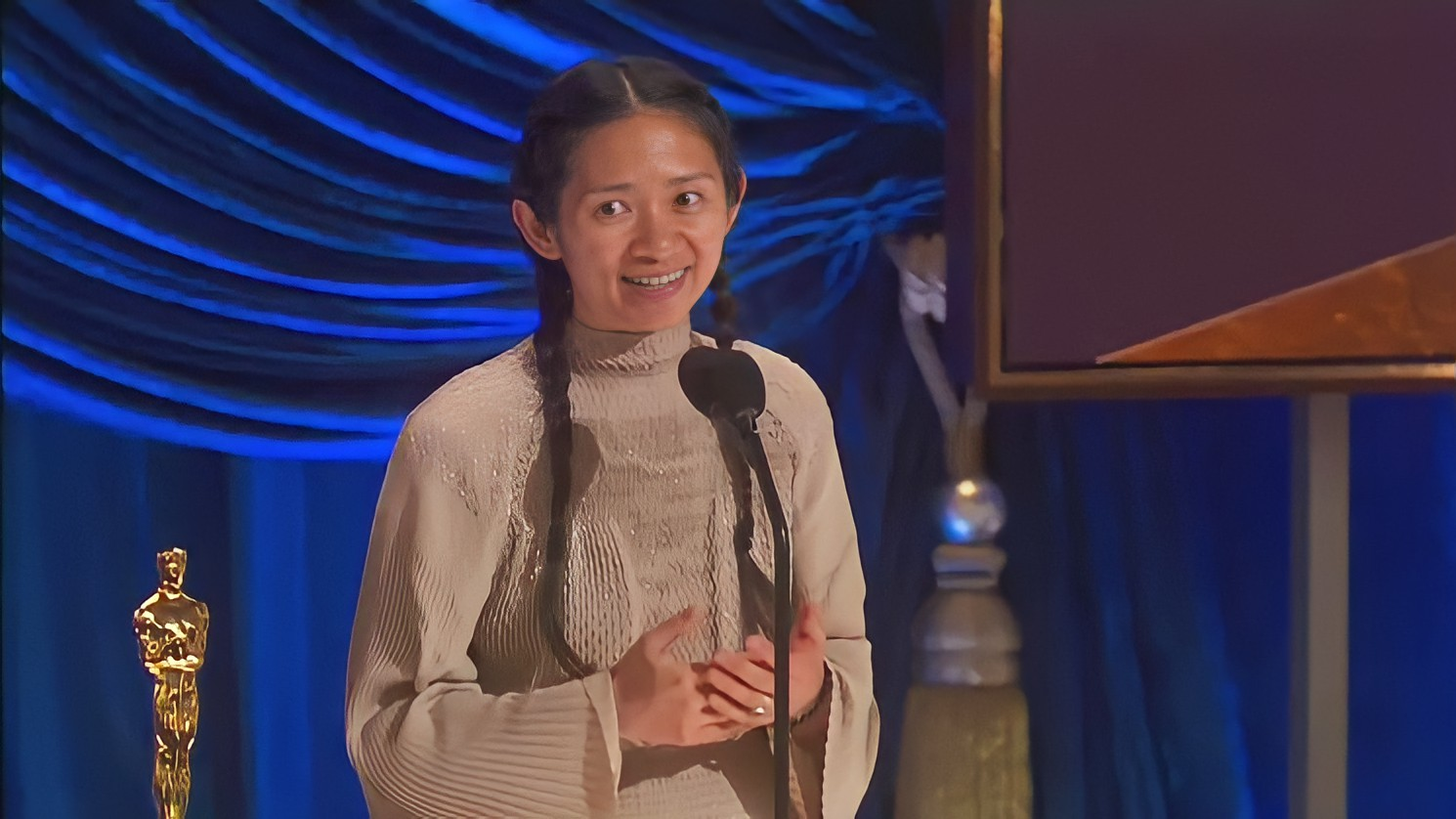 Foto de Chloé Zhao. A mulher asiática usa um vestido bege e seus cabelos pretos estão presos em duas tranças. Ela olha para a esquerda enquanto fala no microfone à sua frente. Do seu lado esquerdo, há uma estatueta. O fundo é azul, com uma tela vinho e laranja.