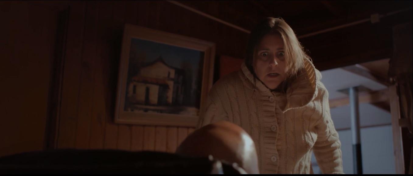 Cena do curta El Campo Sangriento. Nela, vemos Lidia, chilena de cabelo preto e blusa branca, assustada olhando o marido, que está sentado na poltrona.