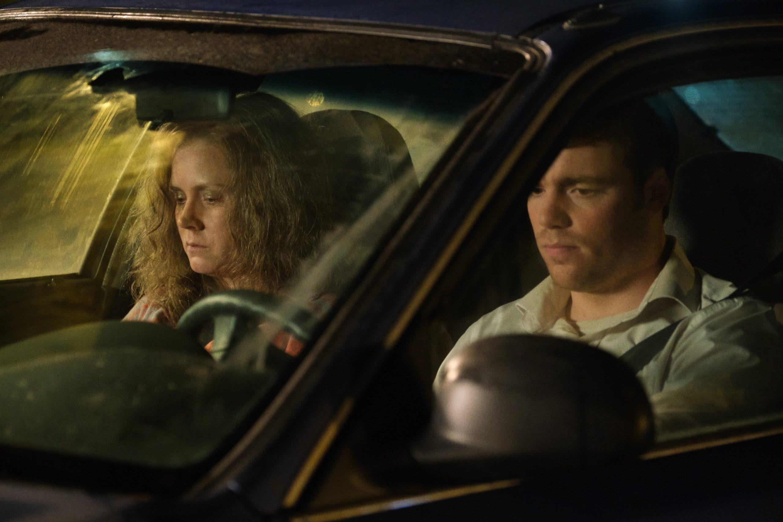 A imagem é uma cena do filme Era uma vez um sonho. Na imagem, estão os personagens Bev e J. D. Vance dentro de um carro. No volante, à direita, está J. D. Vance, interpretado pelo ator Gabriel Basso. Ele é um homem branco, de cabelos castanhos claros; ele veste uma camisa branca. À esquerda, no banco do carona, está Bev, interpretada pela atriz Amy Adams. Ela é uma mulher branca, de cabelos ruivos e compridos; ela veste uma camisa xadrez.