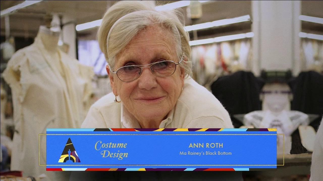 """Foto de Ann Roth. A senhora branca, de cabelos brancos curtos, veste uma blusa também branca e óculos de armação prateada. O fundo possui alguns manequins e roupas, parecendo ser um ateliê. No canto inferior da foto, há um quadado azul, onde """"Costume Desing"""", """"ANN ROTH"""" e """"Ma Rainey's Black Bottom"""" estão escritos de amarelo. No canto esquerdo do quadrado, há um logo colorido do oscar."""