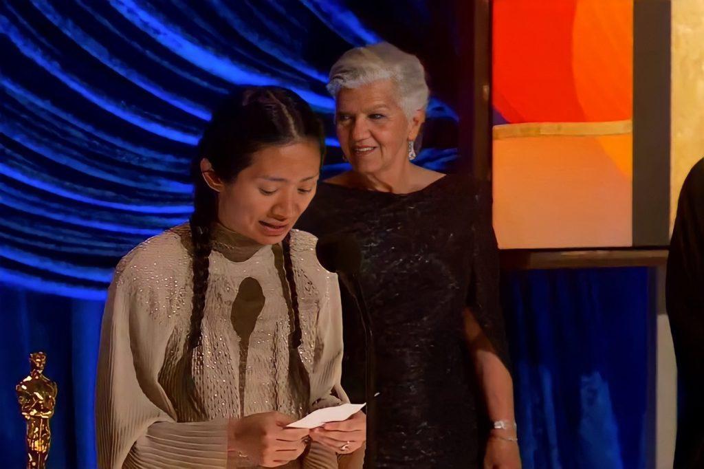 Foto de Chloé Zhao. A mulher asiática lê um papel à sua frente, enquanto discursa no microfone. Ela veste um vestido bege e usa seu cabelo preso em duas tranças. Atrás dela há outra mulher de sua equipe, branca e de cabelos grisalhos, usando um vestido preto. No canto inferior esquerdo é possível ver uma estatueta, e o fundo da imagem é azul.