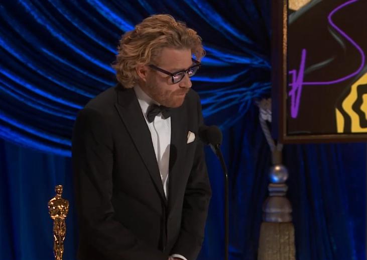 Foto de Erik Messerschmidt. Homem branco, de óculos e cabelos loiros compridos e barba, ele veste um terno preto por cima de uma camisa branca. Erik discursa no microfone a sua frente, e a estatueta descansa ao seu lado esquerdo. O fundo é azul, com uma tela colorida.