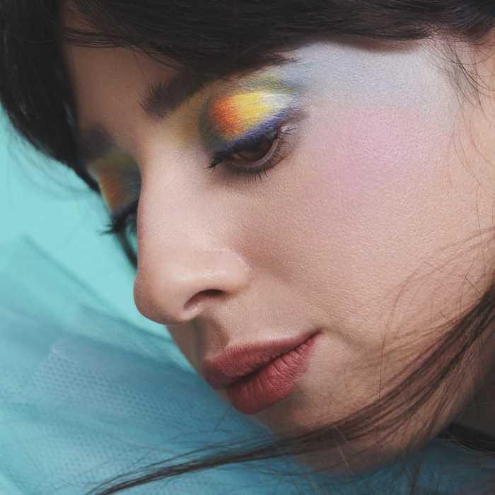 """Capa do EP """"Friends In The Corner"""", da cantora Foxes. A face da cantora ocupa quase todo o espaço da capa, virada para a esquerda e com os olhos mirando para baixo. Uma maquiagem multicor adorna suas pálpebras e seus cabelos pretos e lisos enquadram seu rosto. Atrás dela, um tecido azul-claro e leve ondula levemente."""