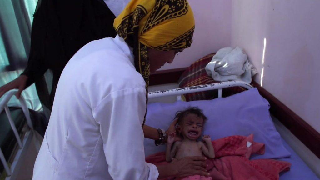 Cena de Hunger Ward. Na imagem, a enfermeira Mekkia Mahdi, uma mulher de pele amarronzada, vestindo um jaleco branco e um hijab amarelo com estampas pretas, se inclina sobre um leito hospitalar, em que uma criança muito magra chora.