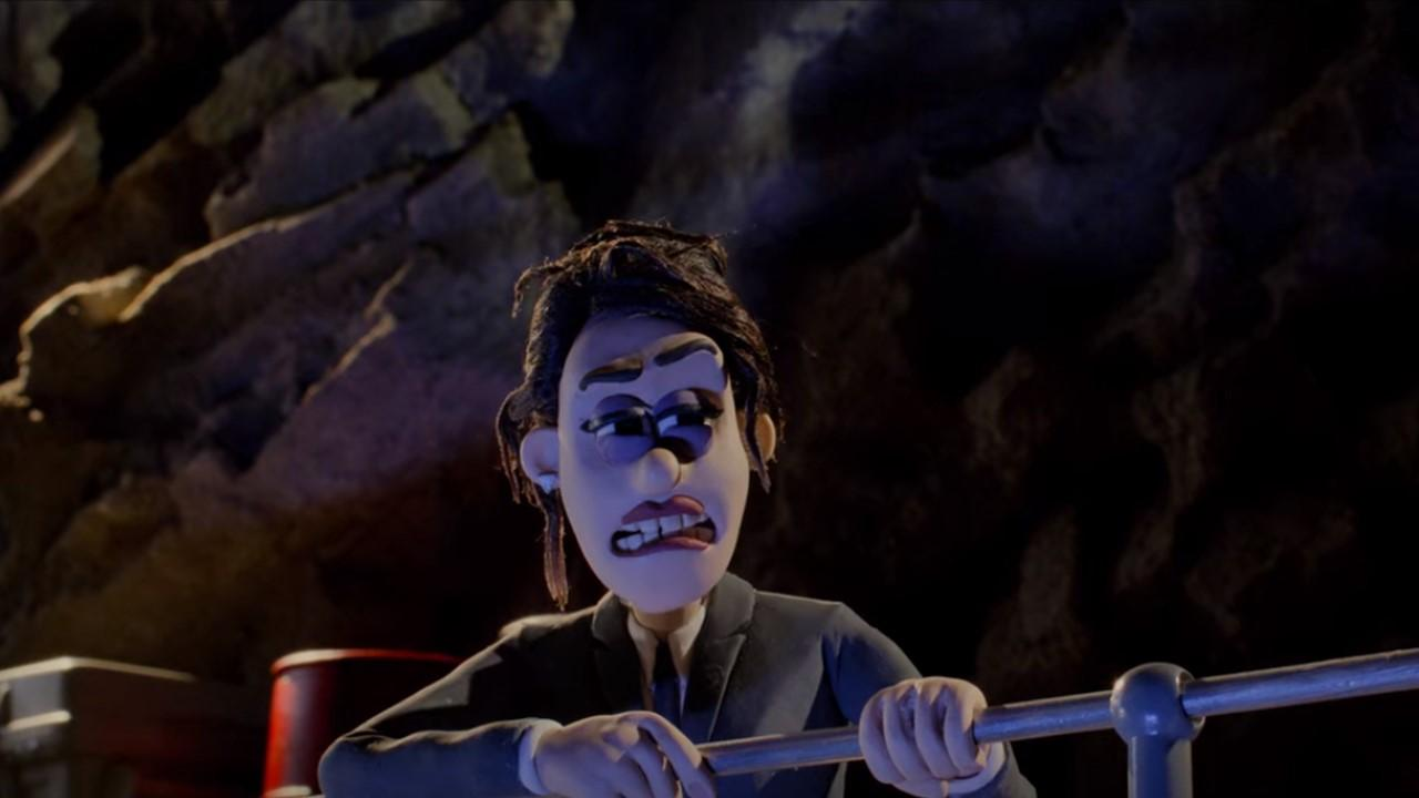 A diretora da M.D.A Red, que é uma mulher branca, de cabelos preto, e que usa um terno preto, está levantando escorada em um corrimão, descabelada, com os olhos cerrados e boca trêmula, se recompondo de um tombo. Ela está em uma caverna.