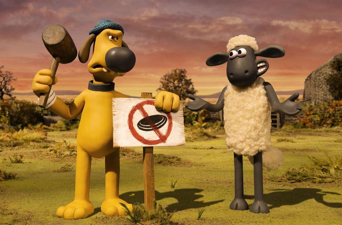 """O cão Blitzer de pelagem amarela e gorro azul, está pregando uma placa no chão com um grande martelo de madeira. Ele está com cara fechada, olhando para Shaun. Na placa, uma imagem de um frisbee com um círculo de """"proibido"""". Shaun, uma ovelha magra de pele preta e pelagem branca, olha com um sorrisinho e mãos levantadas, com um ar de sem graça. Eles estão em um pôr do Sol na fazenda."""