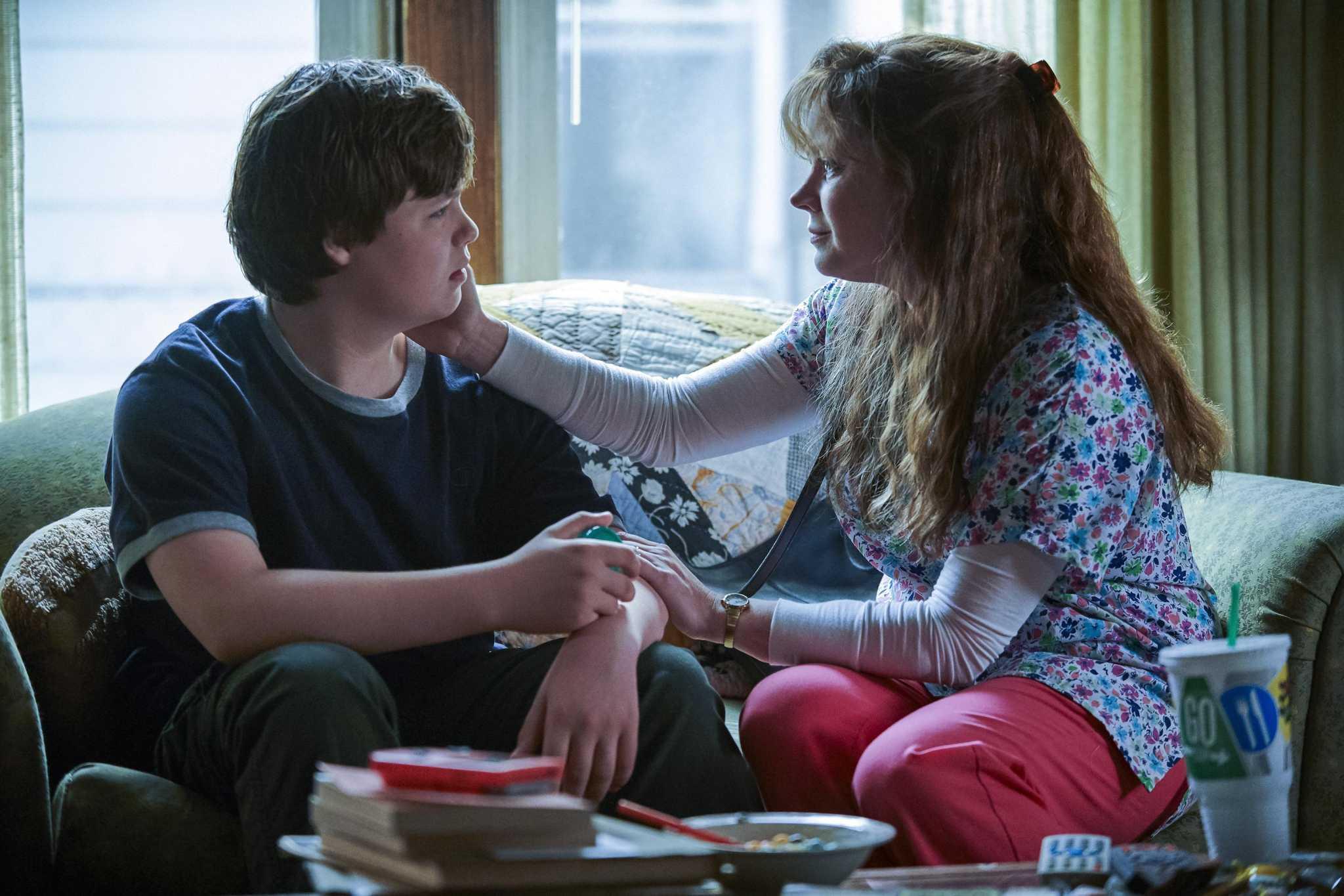 A imagem é uma cena do filme Era uma vez um sonho. Nela, vemos os personagens J. D. e Bev sentados em um sofá. J. D. é interpretado pelo ator-mirim Owen Asztalos; ele está sentado à esquerda, olhando para Bev. Owen é um menino branco, de cabelos castanhos claros, ele veste uma camiseta azul e calças verde-escuro. Bev é interpretada pela atriz Amy Adams, ela está sentada à direita, olhando para Owen com a sua mão direita encostada na bochecha de Owen. Amy é uma mulher branca, de cabelos ruivos e compridos; ela veste uma camiseta florida, com uma blusa branca de mangas compridas por baixo e uma calça rosa.