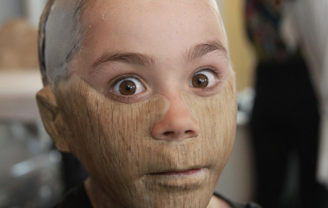 Cena dos bastidores do filme Pinóquio. Nela vemos o ator Federico Ielapi se produzindo para o seu personagem, o Pinóquio. Federico lelapi é um menino de 10 anos, branco e com olhos castanhos claro. Na foto ele está sendo caracterizado como um boneco de madeira, então seu rosto está sendo maquiado com tintas que aparentam ser madeira. Os seus olhos estão bem abertos e olhando diretamente para a câmera.