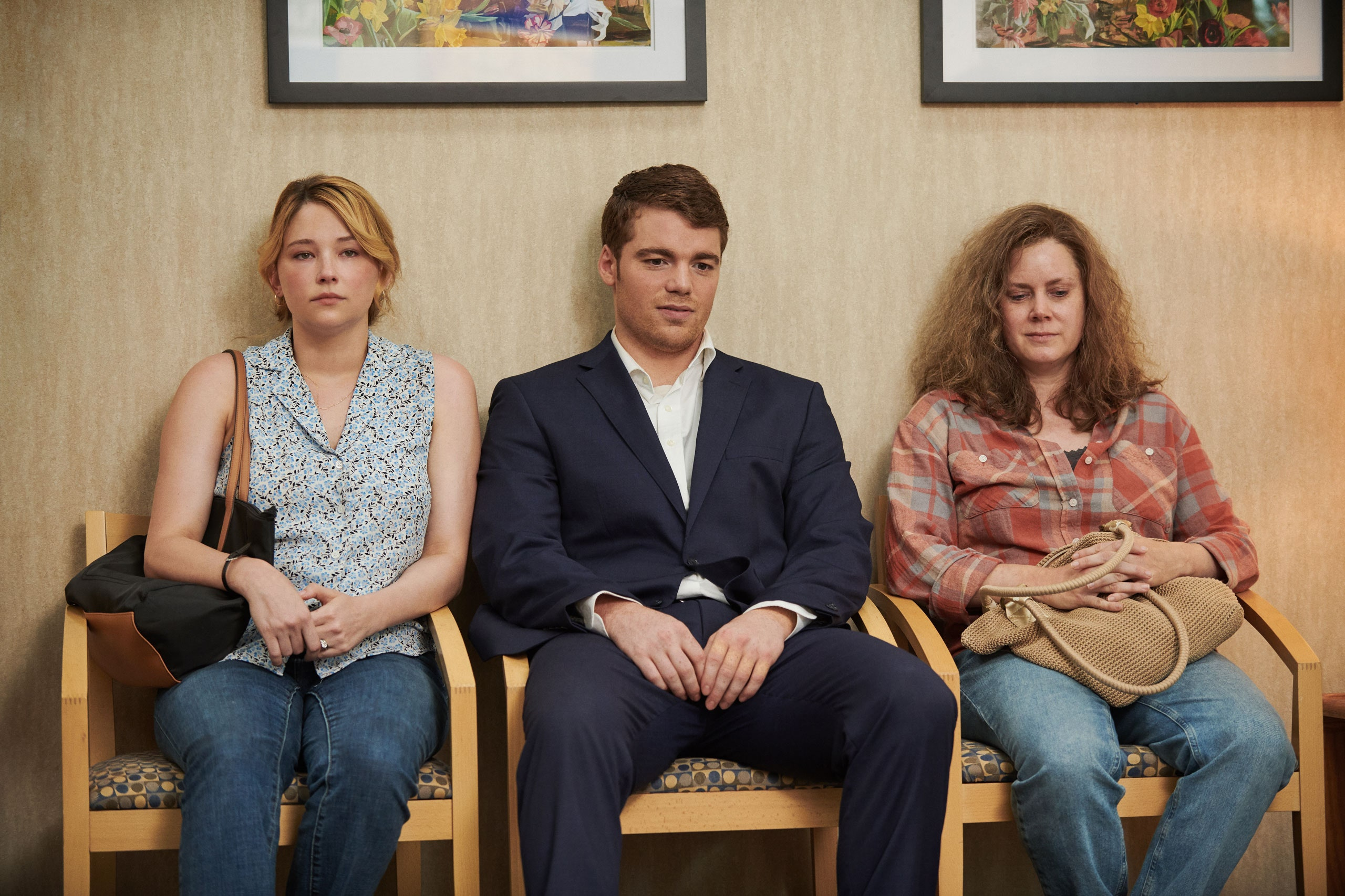 A imagem é uma cena do filme Era uma vez um sonho. Na imagem, os personagens Lindsay, J.D. e Bev estão sentados em cadeiras na sala de espera de um consultório. Na imagem, da esquerda para a direita, está Lindsay, interpretada pela atriz Haley Bennett. Ela é uma mulher branca, com cabelos loiros amarrados em um coque baixo; ela veste uma blusa azul-clara e uma calça jeans, e está com uma bolsa em seu ombro direito. Ao seu lado, está J. D., em sua fase adulta, interpretado pelo ator Gabriel Basso. Ele é um homem branco, de cabelos castanhos claros; ele veste um terno azul-marinho, com uma camisa branca por baixo e uma calça social na cor azul-marinho. Ao seu lado, está Bev, interpretada pela atriz Amy Adams. Ela é uma mulher branca, de cabelos ruivos e compridos; ela veste uma camisa xadrez e uma calça jeans, e está com uma bolsa bege em seu colo.
